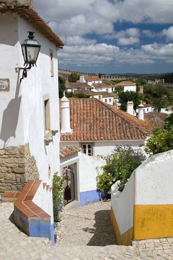 "Street in Obidos (Portugal) - Obidos is a small town in Portugal (its population is slightly over 3000 people) on the Atlantic Ocean. The name comes from Latin and means ""citadel"" (Obidos was built around the former Roman fort (10×15)"