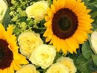 Gele zonnebloemen en rozen