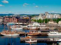 Boats in a harbor with Oslo city hall in the background (Norway)