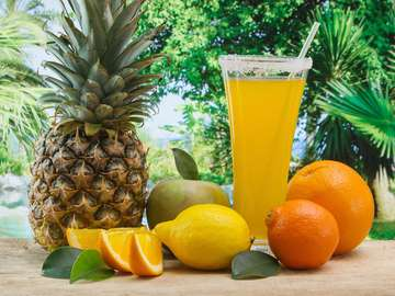 Glass of juice surrounded by tropical fruits