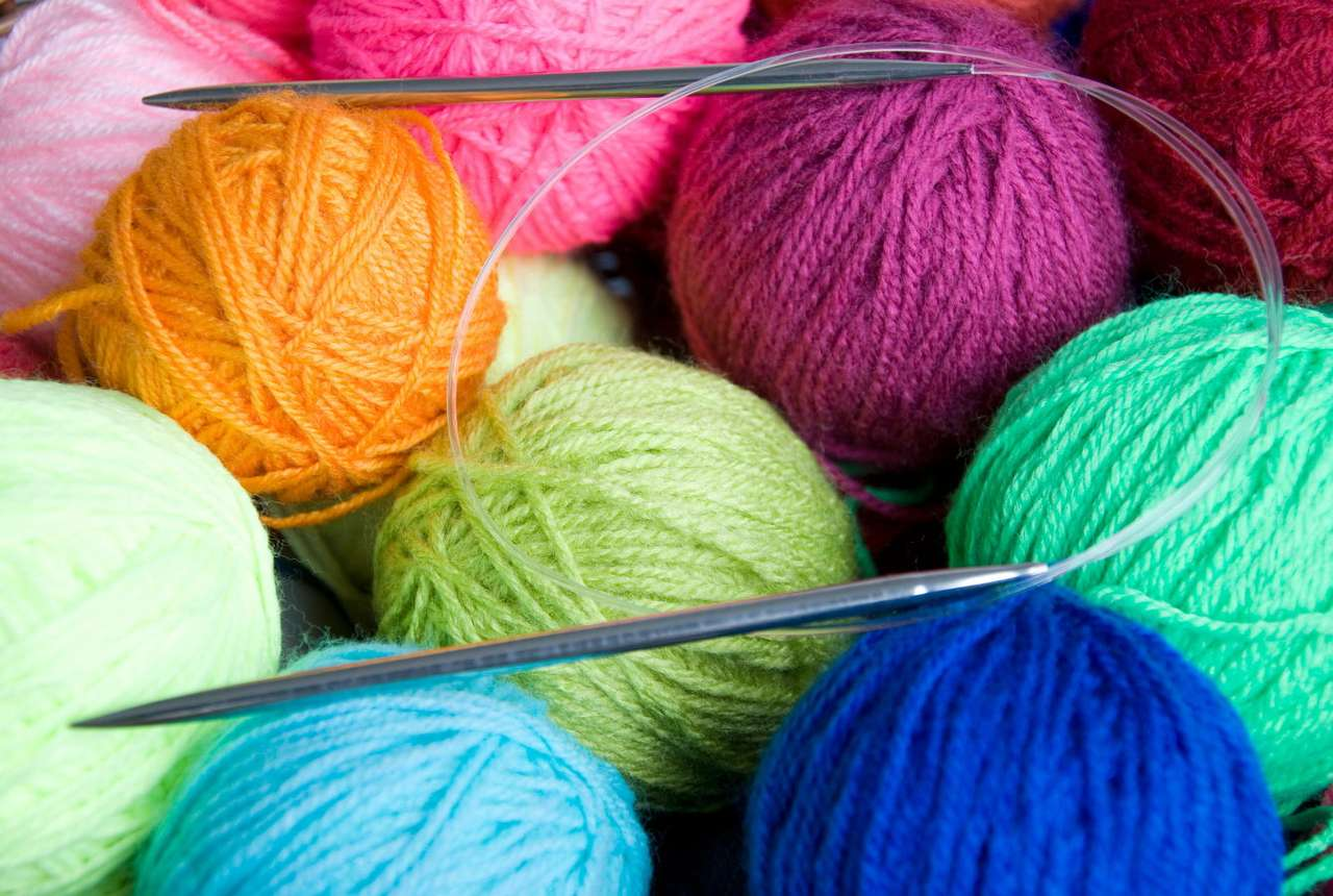 Knitting needles against the background of colorful balls of wool