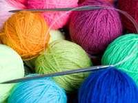 Игли за плетене на фона на цветни топчета вълна