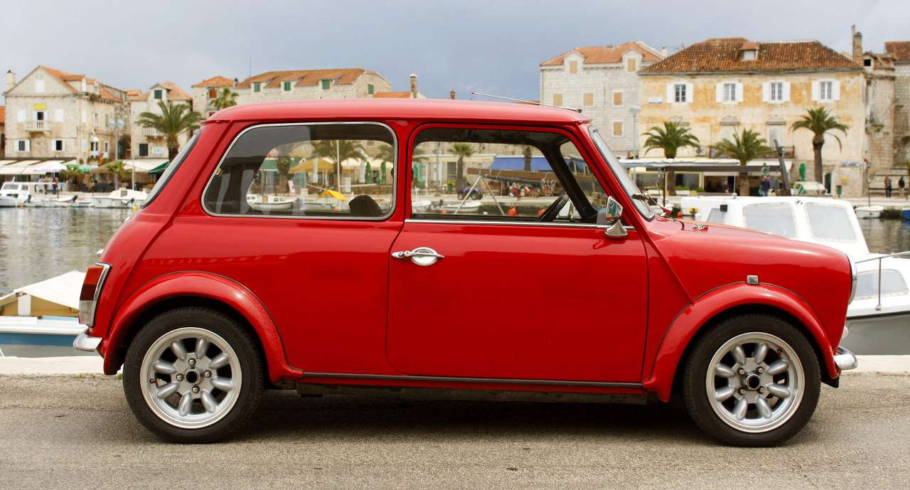 Red Mini 1000 car in a Mediterranean village - Mini is a compact car produced by the British Motor Corporation from 1959 until 2000. It became a cult car in the 1960s and according to the jury of a prestigious automobile competition it was conside (11×6)