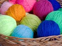 Skeins of colorful wool in a wicker basket