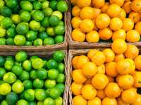 Limes and oranges in baskets at a market stall