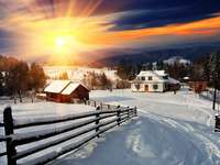 Sunset over a mountain village covered with snow