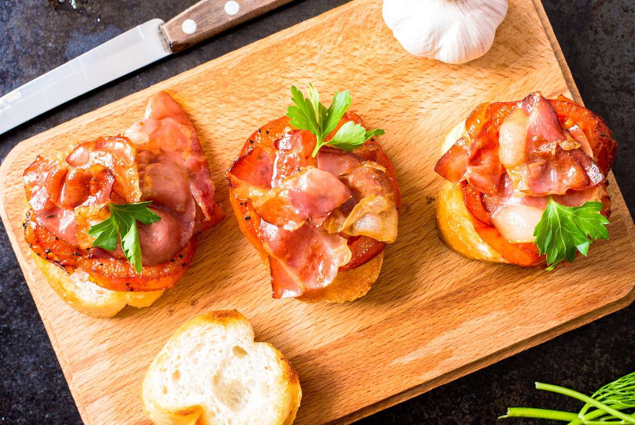 Toasts with bacon and tomatoes - In Italy, a hot toasted snack is called bruschetta. Toasted bread with olive and garlic is usually accompanied by tasty and uncomplicated ingredients such vegetables, fresh herbs, cold cuts or cheese (10×8)