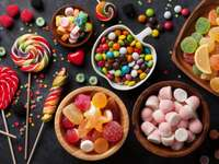 Colorful candies, lollipops and jelly on a dark worktop