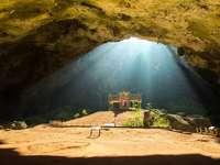 Pavilhão budista dourado em caverna selvagem, Tailândia